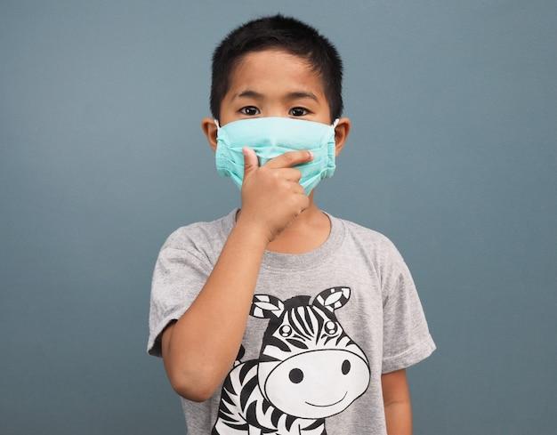 Een jongen die een beschermend masker draagt, terwijl hij zijn hand bedekt terwijl hij hoest.
