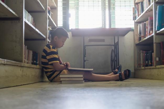 Een jongen die een boek in de bibliotheek leest