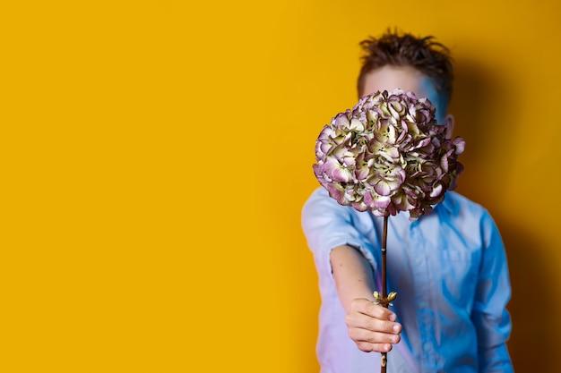 Een jongen die een boeket voor zijn gezicht op een heldere gekleurde achtergrond houdt