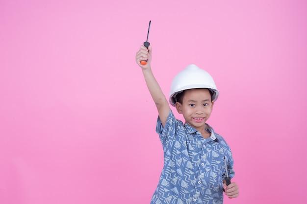 Een jongen die een gebaar uit zijn handen maakte met een helm op een roze achtergrond.