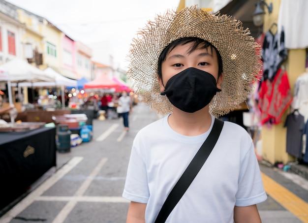 Een jongen die een gezondheidsmasker draagt om het virus te beschermen tijdens het reizen, nieuw normaal Premium Foto