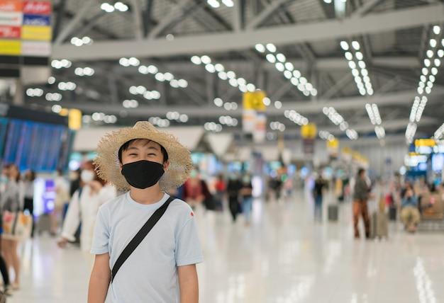 Een jongen die een gezondheidsmasker draagt om per luchthaven te reizen Premium Foto