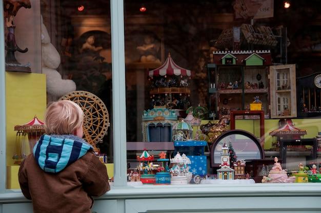 Een jongen die in een winkelvenster kijkt