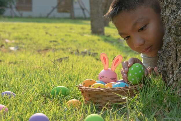 Een jongen die kleurrijk ei in park verzamelt.