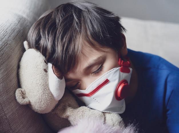 Een jongen die moe is van hoesten op de borst en een gezichtsmasker draagt om pm2.5 te beschermen, kind valt in slaap tijdens het spelen met speelgoed, kind blijft thuis voor bescherming coronavirus, griepuitbraak en ziektebeschermingsconcept