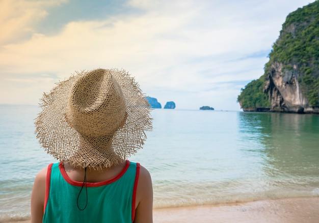 Een jongen die strandhoed draagt voor vakantie aan zee Premium Foto