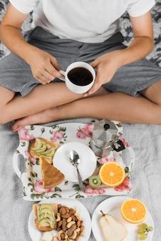 Een jongen die zwarte koffiekop in zijn hand houdt die gezond ontbijt heeft