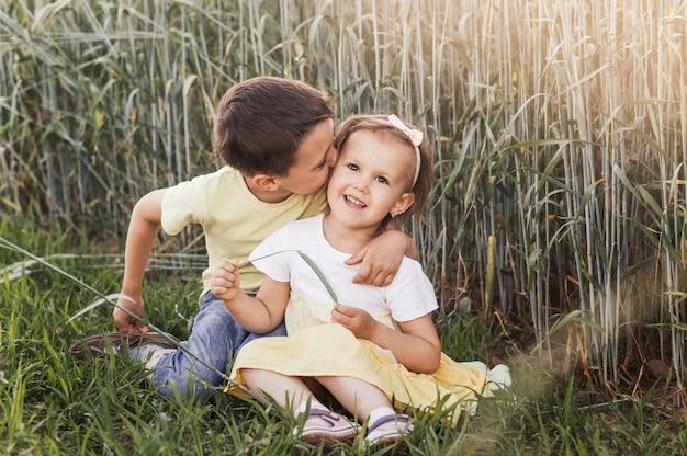 Een jongen en een meisje, broer en zus spelen in de zomer in het veld. fijne zomervakantie. jongen en meisje op landweg. tarwe veld