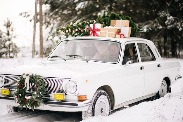 Een jongen en een meisje gaan in een retro-auto versierd met een kerstboom