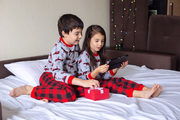 Een jongen en een meisje in een rode en grijze pyjama zitten thuis op het bed