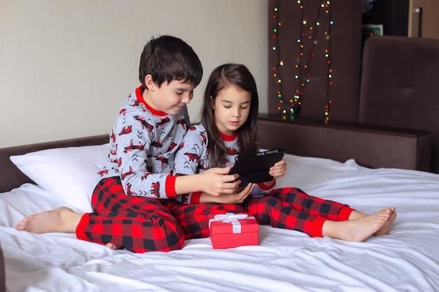 Een jongen en een meisje in rode en grijze pyjama's zitten thuis op het bed, glimlachen naar een digitale tablet