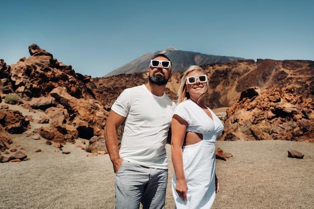 Een jongen en een meisje in witte kleren en glazen staan in de krater van de el teide-vulkaan