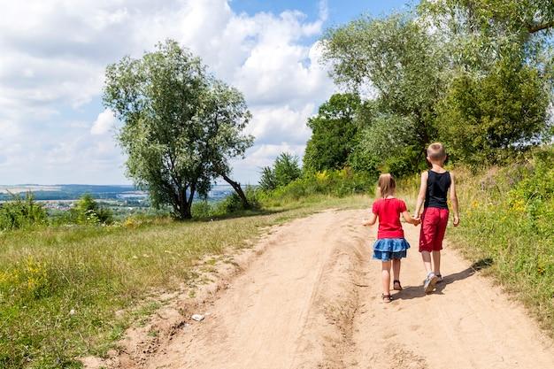 Een jongen en een meisje kinderen lopen op een onverharde weg op een zonnige zomerdag.