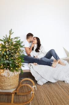 Een jongen en een meisje knuffelen en kussen terwijl ze in de winter thuis op het bed zitten