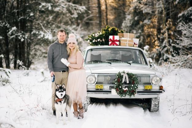 Een jongen en een meisje maken zich klaar voor kerstmis, wandelen met de husky hond op een achtergrond van vintage auto, op de dakboom en geschenken in het besneeuwde winterbos