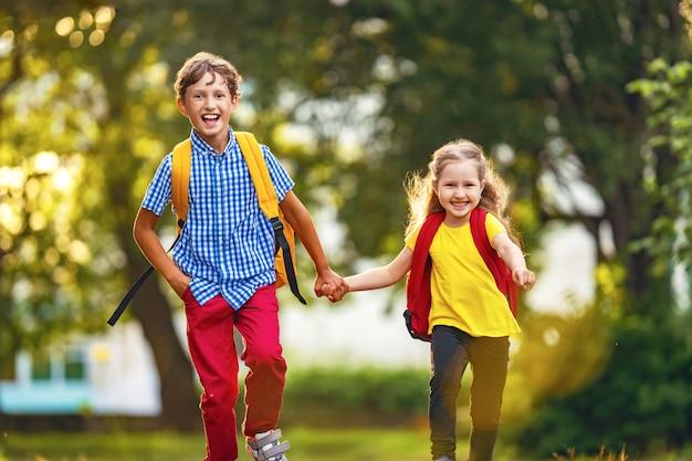 Een jongen en een meisje met rugzakken lopen over straat