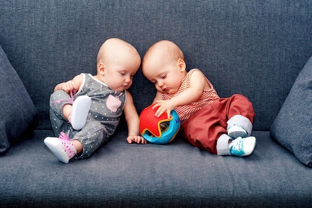 Een jongen en een meisje met speelgoed tot een jaar op de bank. het concept van een tweeling in de familie.