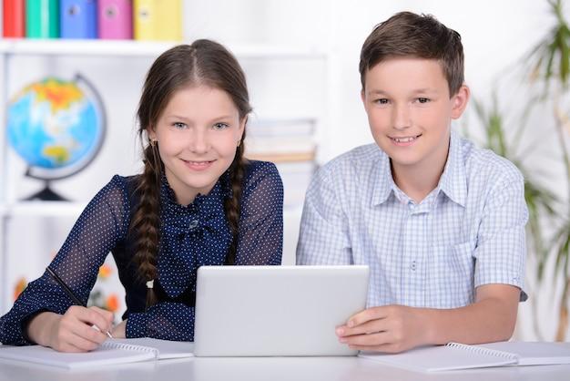 Een jongen en een meisje onderzoeken de tablet.