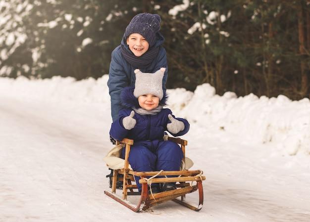 Een jongen en een meisje slee in de winter in de natuur. broer en zus samen
