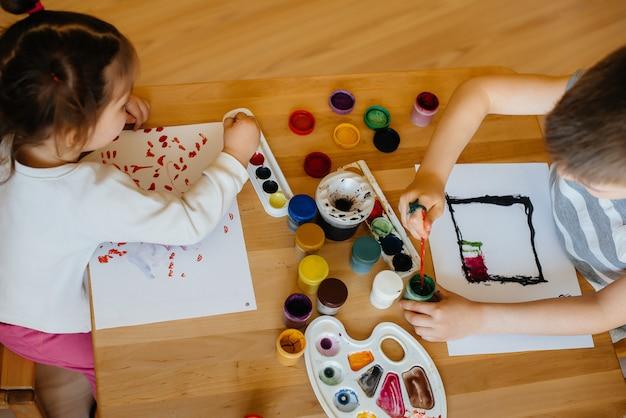 Een jongen en een meisje spelen samen en schilderen. recreatie en amusement. blijf thuis.