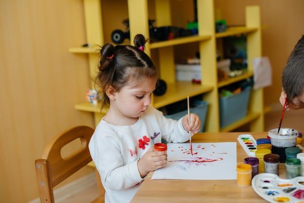 Een jongen en een meisje spelen samen en schilderen. recreatie en entertainment. blijf thuis.