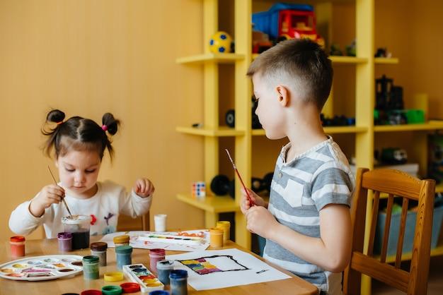 Een jongen en een meisje spelen samen en schilderen. recreatie en vermaak. blijf thuis.