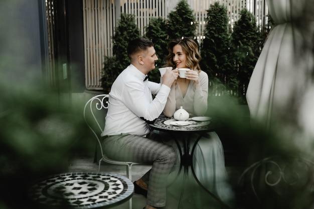 Een jongen en een meisje zitten aan een tafel in een restaurant op straat en drinken thee. romantische date van een verliefd stel.