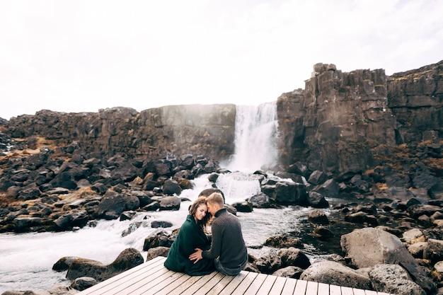 Een jongen en een meisje zitten elkaar omhelzend op een brug bij de ehsaraurfoss-waterval