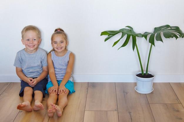Een jongen en een meisje zitten op de grond. kinderen samen thuis