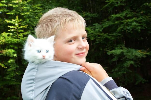 Een jongen en een wit katje in de kap. in de natuur.