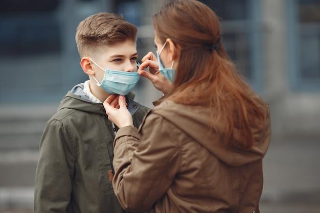Een jongen en moeder dragen beschermende maskers