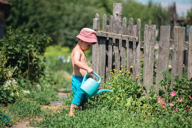 Een jongen geeft bloemen in de tuin water.