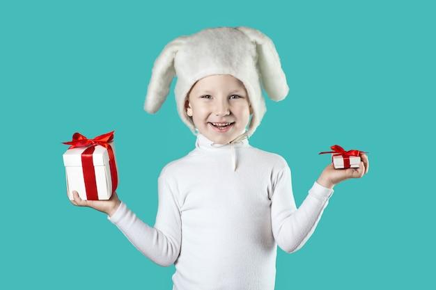 Een jongen gekleed als een witte haas probeert een geschenk op mint achtergrond te kiezen