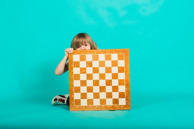 Een jongen houdt een schaakbord in zijn handen en kijkt ernaar, emotioneel poserend