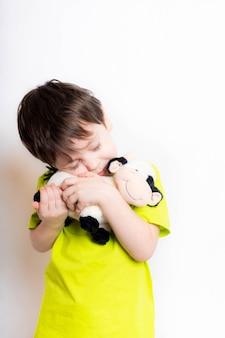 Een jongen houdt een stierenspeelgoed vast. leuk kind met een stuk speelgoed. speelgoedstier, symbool van het jaar. 2021. nieuwjaar. leuke emoties