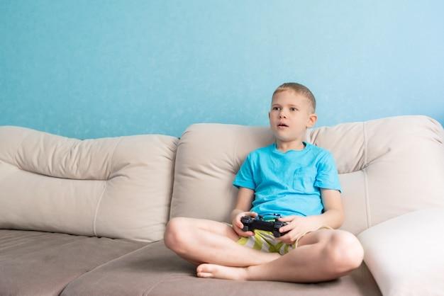 Een jongen in blauw t-shirt heeft een joystick om te spelen