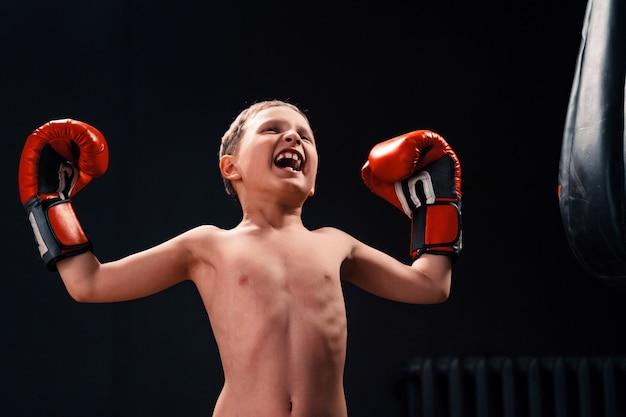 Een jongen in de buurt van een bokszak in bokshandschoenen schreeuwt en steekt zijn handen op als winnaar van een tinnen leider.