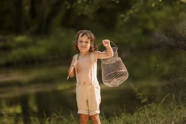 Een jongen in de buurt van rivieren zomer in het bos met toverstaf in plaats van hengels