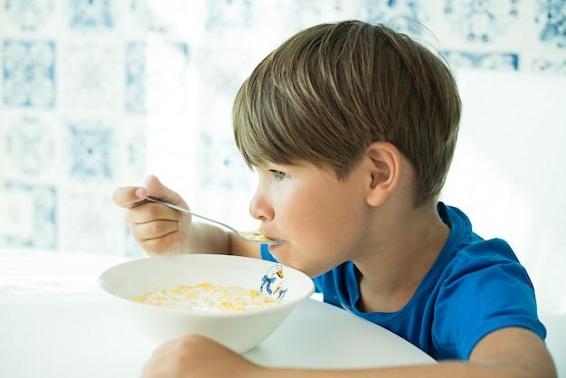 Een jongen in een blauw t-shirt heeft ontbijt met havermout en melk in een witte plaat, ruimte voor tekst, isoleren