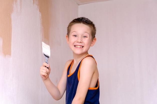 Een jongen in een blauw t-shirt schildert de binnenmuur van het appartement