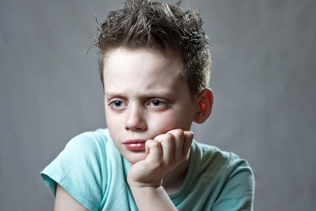 Een jongen in een fel t-shirt beledigd en huilend