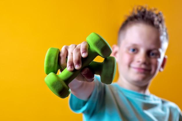 Een jongen in een fel t-shirt met halters op een geel
