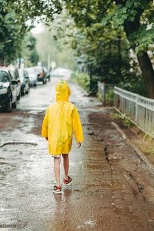 Een jongen in een gele regenjas komt naar buiten in de regen. kind loopt alleen in de regen. achteraanzicht in een lichte regenjas. in plassen lopen