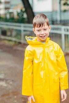 Een jongen in een gele regenjas loopt buiten in de regen. mooi en lachend kind op straat. portret van een jongen van europese ongemakkelijkheid. open glimlach van een kind