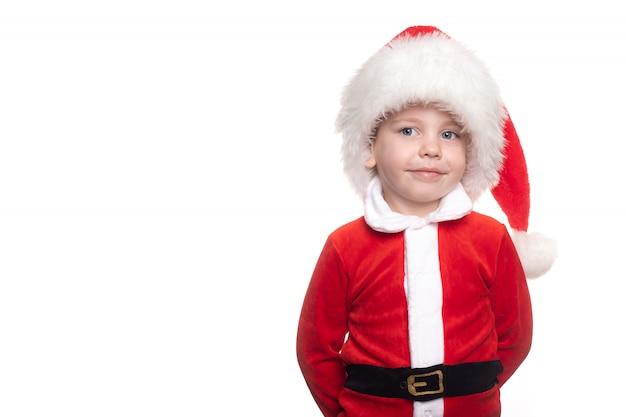 Een jongen in een kerstman pak op een witte achtergrond kijkt in het frame.
