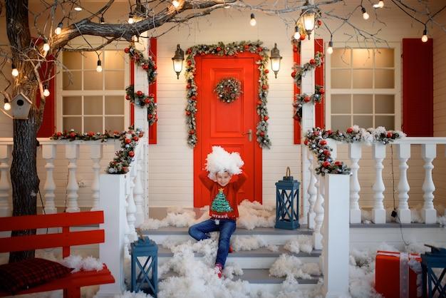 Een jongen in een kersttrui zit op de trappen van een huis