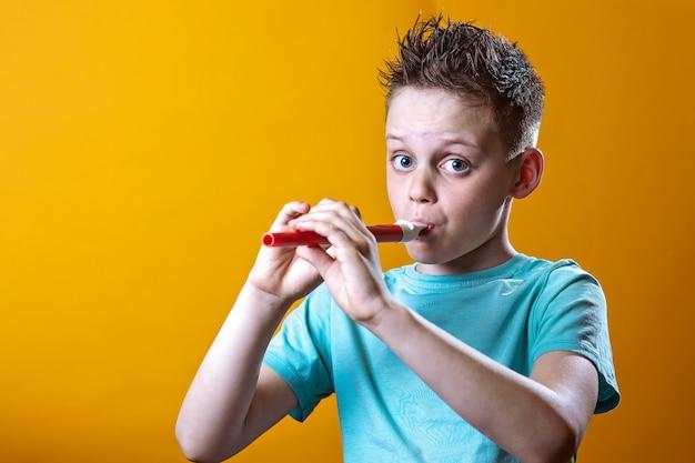 Een jongen in een licht t-shirt die op een pijp op gekleurd speelt