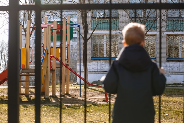 Een jongen in een medisch masker kijkt tijdens quarantaine over een metalen hek naar een speeltuin