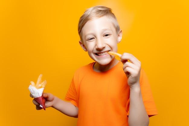 Een jongen in een oranje t-shirt houdt een zak gefrituurde aardappelen voor zich en bijt glimlachend in een stuk aardappelen