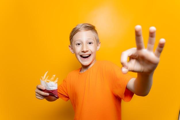 Een jongen in een oranje t-shirt houdt een zak gefrituurde aardappelen voor zich en maakt een ok-gebaar naar de camera